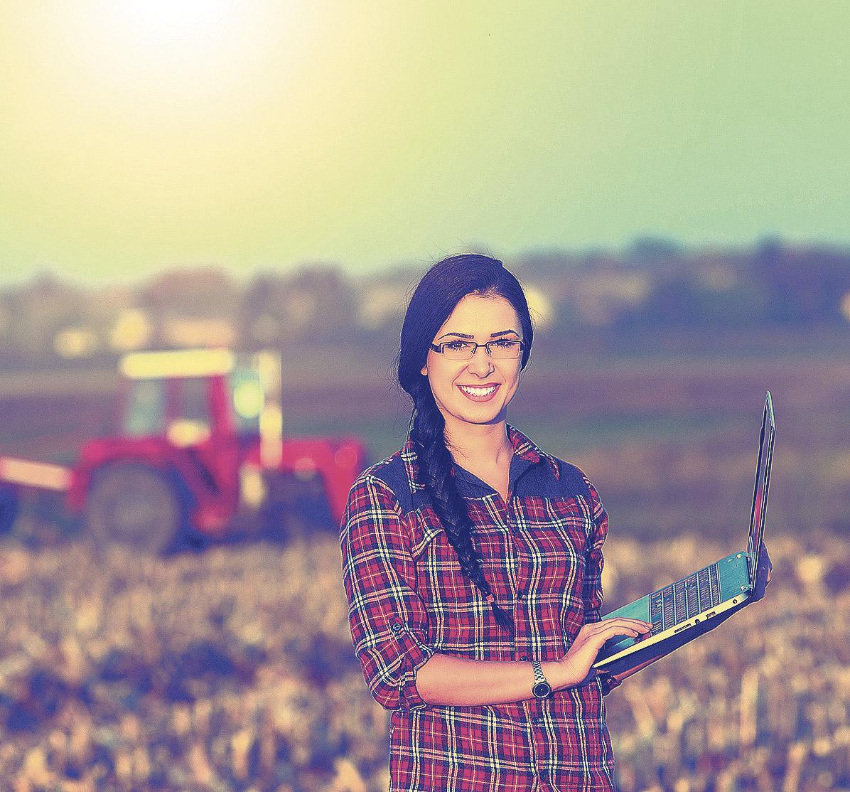 Frau mit Laptop auf einem Acker, Thema: Nachhaltige Energieversorgung auf dem Land