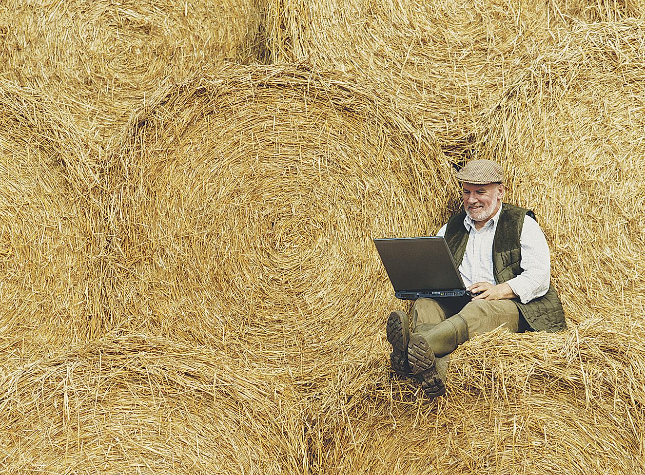Bauer sitzt mit einem Laptop vor einem Heuballen; Thema: Landmaschinentechnik