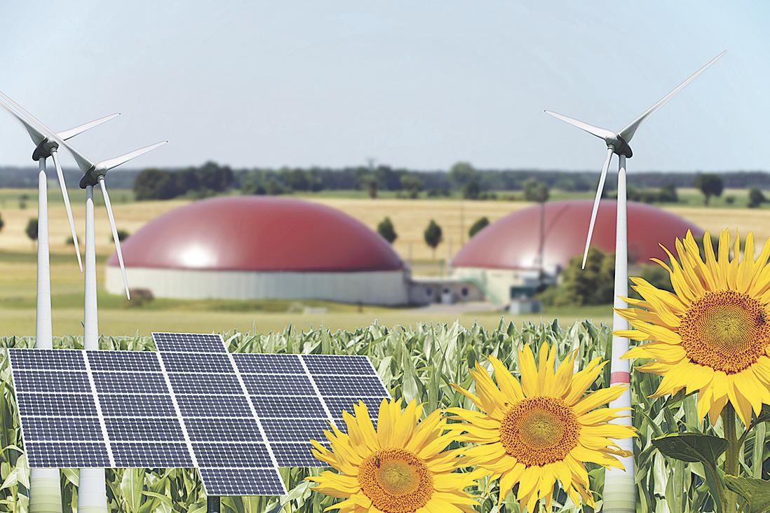 Solarkollektoren und Windräder vor einem Bauernhof; Thema: Biogas