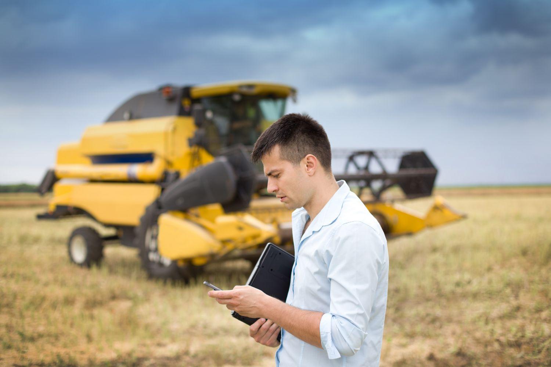 Bauer mit Smartphone in der Hand vor einem modernen Traktor