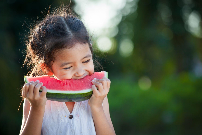 Ein Mädchen beißt in ein Stück Wassermelone. Thema: Nachhaltige Landwirtschaft