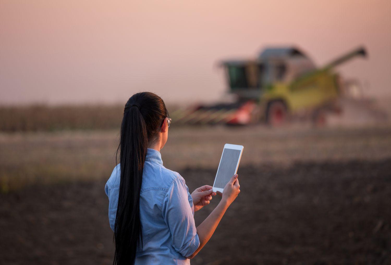 Eine Frau steht mit einem Tablet auf dem Feld. Hightech ist in der Landwirtschaft auf dem Vormarsch