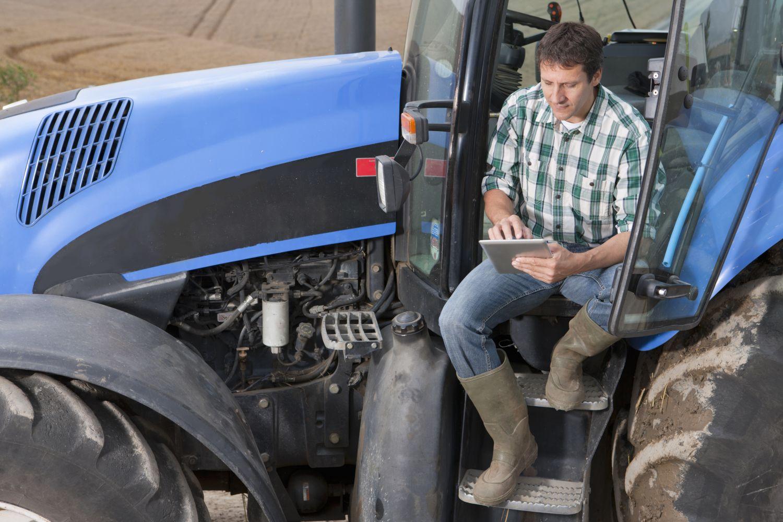 Landwirt auf Traktor nutzt ein Tablet für seine Arbeit
