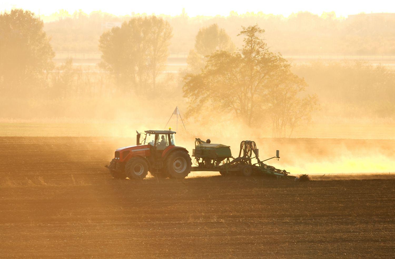 Traktor wirbelt Staub auf während er über das Feld fährt.