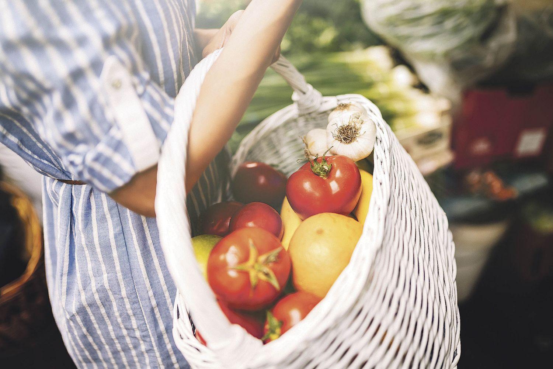 Eine Frau hält einen Korb mit Früchten. Thema: Qualität von Bioprodukten